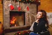 Beautiful woman near fireplace — Stock Photo