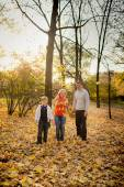 Happy family throws yellow leaves — Stock Photo