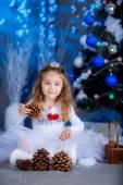Girl sits near Christmas tree — Stock Photo