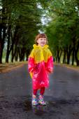 Little girl in rubber boots jumping in puddles — Stock Photo