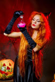 Red-haired girl in the image of the witch. — Stock Photo
