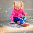 Little girl draw with crayons on the pavement — Stock Photo #56606961