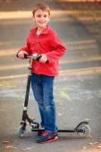 Boy riding a kick scooter — Stock Photo