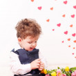 Curly-haired boy with a bouquet of tulips. — Stock Photo #64393927