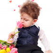 Curly-haired boy with a bouquet of tulips. — Stock Photo #64393935