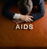 Word AIDS and devastated man composition — Stock Photo
