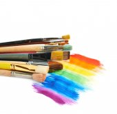 Pile of different brushes over the paint strokes — Stock Photo