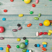 Candies lying over the wooden surface — Stock Photo
