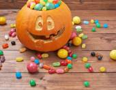 Jack o lantern pumpkin filled with candies — Stock Photo