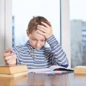 Boy sitting over the pile of homework — Stock Photo