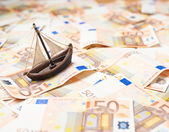 Tiny ship over the bank note bills — Stock Photo