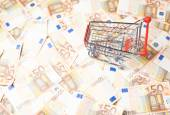 Shopping cart over the bank note bills — Stock Photo