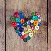 Vintage buttons in the shape of a heart on a wooden  background — Stock Photo