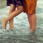 Young couple in love hugging and kissing on the beach. — Stock Photo