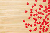 Red hearts confetti on wooden background — Stock Photo