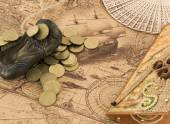 Bronze shoe figure, fan and card on the old map — Stock Photo