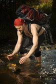 Man in red scarf refreshing in creek — Stock Photo