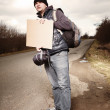 Hitch-hiker waiting for car on route — Stock Photo #67255783