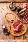 Filete ribeye carne cruda fresca y condimentos sobre fondo de madera — Foto de Stock