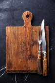 Chopping board, fork and knife — Stock Photo