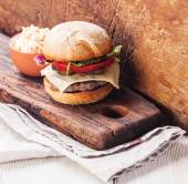Burger with coleslaw on chopping board — Stock Photo