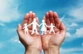 Papier łańcucha rodziny chronione w złożone dłonie — Zdjęcie stockowe