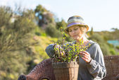 Woman sitting on nature and holding a pot with plant — Stock Photo