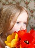 Little blond girl  with tulips — Stock Photo