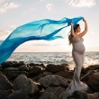 Smiling Pregnant Woman on the Beach with Blue Veil — Stock Photo #57473593