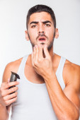 Young handsome man trimming his beard — Stock Photo