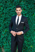Elegant businessman standing on leaves background — Stock Photo