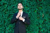 Eleganti uomo d'affari in piedi sullo sfondo di foglie — Foto Stock