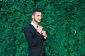 Elegante empresario pisando hojas de fondo — Foto de Stock
