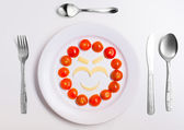 Plate with funny emoticons made from food with cutlery on white — Photo