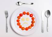 Plate with funny emoticons made from food with cutlery on white — Stock Photo