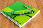 Green diary with black glassess and gold pen on wood table — Foto de Stock