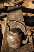 Vecchia caldaia in panchina in legno all'aperto — Foto Stock