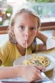 Adorable niña comiendo espaguetis en restaurante al aire libre — Foto de Stock