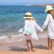 Little cute girls walking on white beach during vacation — Stock Photo #52851285