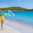 Little pretty girl running along the beach with towel and very happy — Stock Photo #52851411