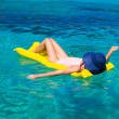 Woman relaxing on inflatable mattress in the sea — Stock Photo #52852471