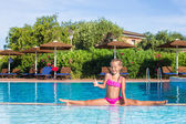 Adorable happy little girl in the swimming pool sitting on the splits — Stock Photo