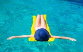 Young attractive girl swimming on an inflatable mattress in the clear sea — Stock Photo
