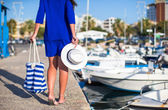Young beautiful woman walking with hat and bag on dock near the boat — Stock Photo