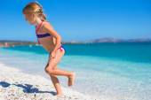 Adorable little girl in shallow water have fun at white beach — Stock Photo