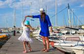 Young mother with little pretty girl in the port enjoying sunny summer day — Stock Photo