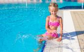Adorable happy little girl in the swimming pool looking at camera — Foto Stock