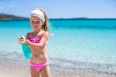 Little adorable girl in swimsuit with suntan lotion bottle — Stockfoto
