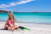 Little girl with flippers and goggles for ssnorkling on the beach — Stock Photo