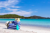 Stripe bag, straw hat, sunblock and towel on white tropical beach — Стоковое фото
